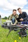 Tekniker som diskuterar över den Digital minnestavlan med UAV royaltyfri bild
