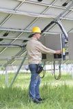 Tekniker som fungerar under sol- paneler Arkivfoton