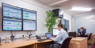 Tekniker som i regeringsställning sitter körande diagnostik arkivbilder