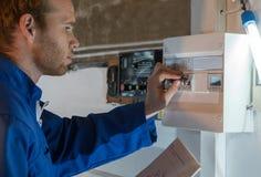 Tekniker som justerar termostaten för uppvärmningsystem Royaltyfri Foto