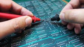 Tekniker som kontrollerar det elektroniska brädet Fotografering för Bildbyråer