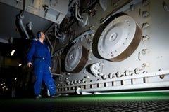 Tekniker som kontrollerar motorinre i frånlands- installation Arkivfoto