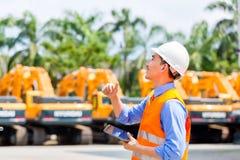Tekniker som kontrollerar plan på konstruktionsplats Arkivfoton