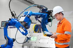 Tekniker som programmerar robotic klipp för kontrolllaser på metallplattan, bransch 4 Uttrycka av rött färgar lokaliserat över te royaltyfri foto