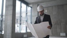 Tekniker som ser byggnadsplan i konstruktionsplats stock video