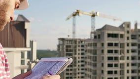 Tekniker som ser på projekt på konstruktionsplats stock video