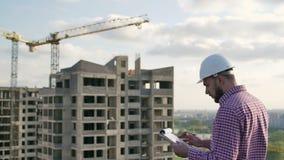 Tekniker som ser på projekt på konstruktionsplats lager videofilmer