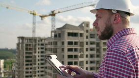 Tekniker som ser på projekt på konstruktionsplats arkivfilmer