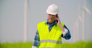 Tekniker som talar på mobiltelefonen mot väderkvarnlantgård arkivfilmer