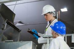 Tekniker som undersöker kött som bearbetar maskinen royaltyfria bilder