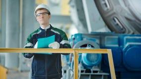 Tekniker som undertecknar ett dokument i industriell fabrik lager videofilmer