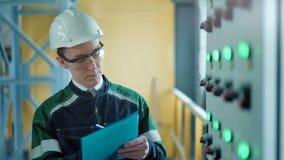 Tekniker som undertecknar ett dokument i industriell fabrik stock video