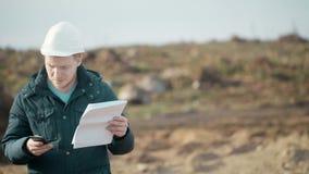 Tekniker Talking Mobile Phone och sedokument på bakgrund av grävskopan fors med glidaren stock video
