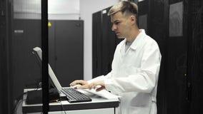 It-tekniker Works på en compuiter i stor datorhall mycket av kuggeserveror Han kör upp diagnostik och underhåll Stets lager videofilmer