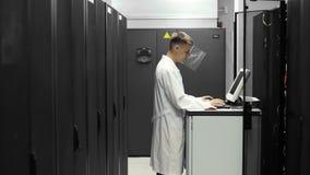 It-tekniker Works på en compuiter i stor datorhall mycket av kuggeserveror Han kör upp diagnostik och underhåll Stets arkivfilmer