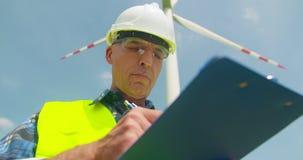 Tekniker Writing On Clipboard, medan göra kontroll för vindturbin arkivfilmer