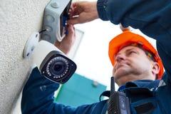 Teknikerarbetare som installerar den videopd bevakningkameran på väggen royaltyfri fotografi