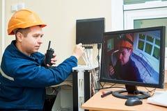 Teknikerarbetare som justerar det videopd bevakningsystemet Arkivbild