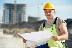 Teknikerbyggmästare på konstruktionsplatsen med utkastet arkivbilder