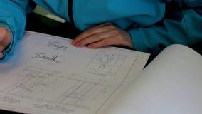 Teknikerbyggmästaren kontrollerar teckningar stock video
