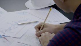 Teknikerbyggmästaren på hans skrivbord utför en blyertspennateckning på papper arkivfilmer