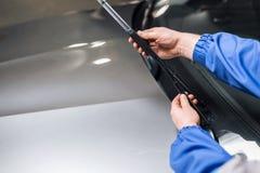 Teknikeren ändrar vindrutatorkare på en bilstation royaltyfri foto
