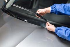 Teknikeren ändrar vindrutatorkare på en bilstation arkivbild