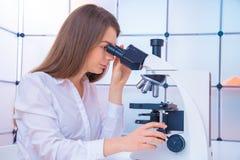 Teknikeren för den unga kvinnan undersöker en histological prövkopia, en biopsi i laboratoriumet av cancerforskning royaltyfri fotografi