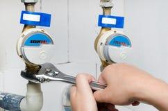 Teknikeren installerar en ny vattenmeter med skiftnyckeln Royaltyfri Foto