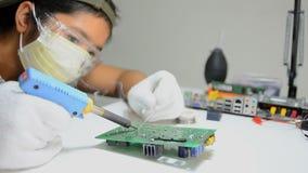 Teknikeren löder till det elektroniska tryckströmkretsbrädet arkivfilmer