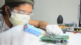Teknikeren löder till det elektroniska tryckströmkretsbrädet lager videofilmer