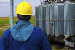 Teknikeren med den gula hjälmen kontrollerar den höga spänningskraftverket royaltyfri bild
