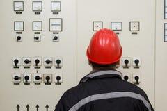 Teknikeren med röd hjälmläsning instrumenterar kraftverket lurar arkivbilder