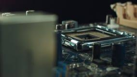 Teknikeren pluggar in CPU-mikroprocessorn till moderkorthåligheten Seminariumbakgrund lager videofilmer