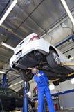 Teknikeren som arbetar på bilen på bilreparationen, shoppar royaltyfri bild