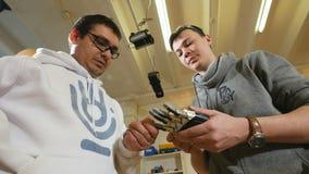 Teknikerer ser den tillverkade robotic bioniska armen som göras på skrivaren 3D stock video