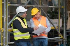 Teknikerer som arbetar på konstruktionsplats Royaltyfri Foto