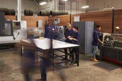 Teknikerer som arbetar på maskiner i upptaget metallseminarium arkivbild