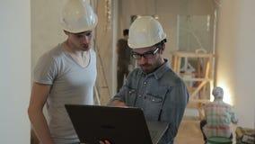 Teknikerer som diskuterar konstruktion av lägenheten i nytt hus lager videofilmer