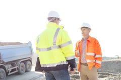 Teknikerer som diskuterar på konstruktionsplatsen mot klar himmel på solig dag arkivbild