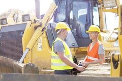 Teknikerer som diskuterar på konstruktionsplatsen Arkivfoton