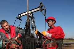 Teknikerer som kontrollerar oljefältutrustning Royaltyfria Foton