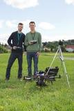 Teknikerer som rymmer fjärrkontroller av UAV arkivbilder