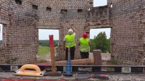 Teknikerer som talar i oavslutad byggnad lager videofilmer