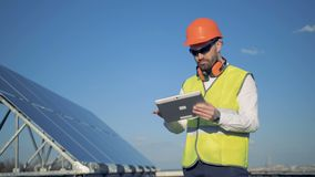 Teknikerer står på ett tak nära solpaneler som arbetar på hans grej 4K arkivfilmer