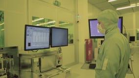 Teknikerforskare i sterila dräkter, maskering var i en ren zon som ser en process flyttade fram technologically, fabriken arkivfilmer