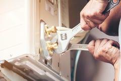 Teknikerhand genom att använda den fasta skiftnyckeln för att dra åt den utomhus- enheten av luft royaltyfria foton