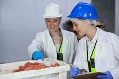 Teknikerhandstil på skrivplattan, medan undersöka kött royaltyfri foto