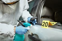 Teknikerkriminolog som arbetar på framkallning av latenta handprints på bildörr arkivfoton