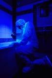 Teknikerkriminolog som arbetar under UV ljus Arkivbild